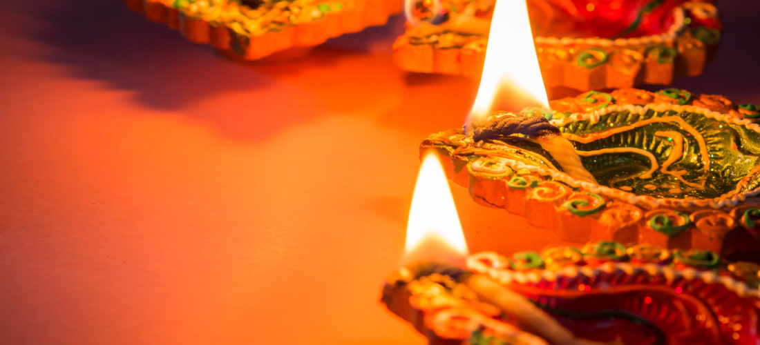 Colorful and sparkling clay diya lamps lit for the Hindu Diwali festival.